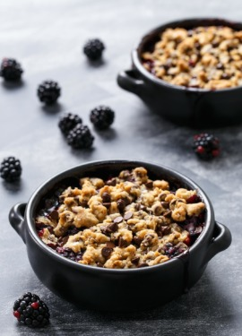 Two black baking dishes with Blackberry Chocolate Chip Cookie Crumble on a chalkboard background