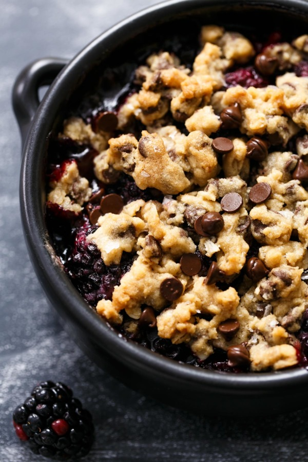 Closeup of baking dish with oatmeal chocolate chip cookie crumble on top of blackberries