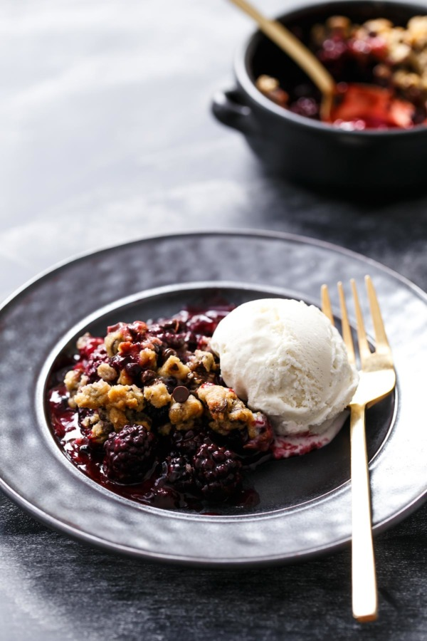 Serving of Blackberry Chocolate Chip Cookie Crumble on a black plate with scoop of vanilla ice cream
