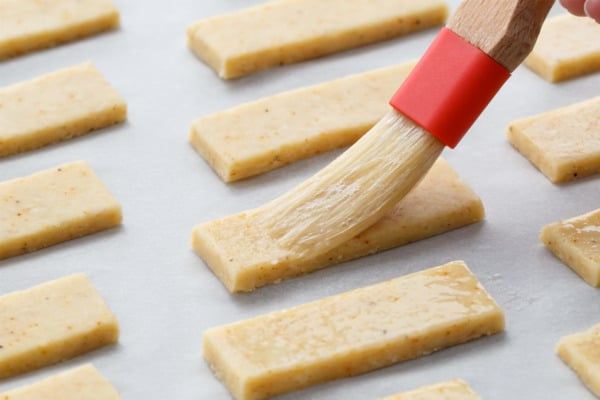 Brushing Parmesan Puffs with egg wash before baking