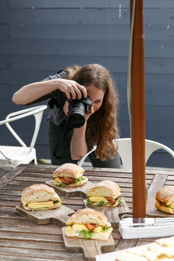 Jen getting the perfect shot of the perfect breakfast sandwich.
