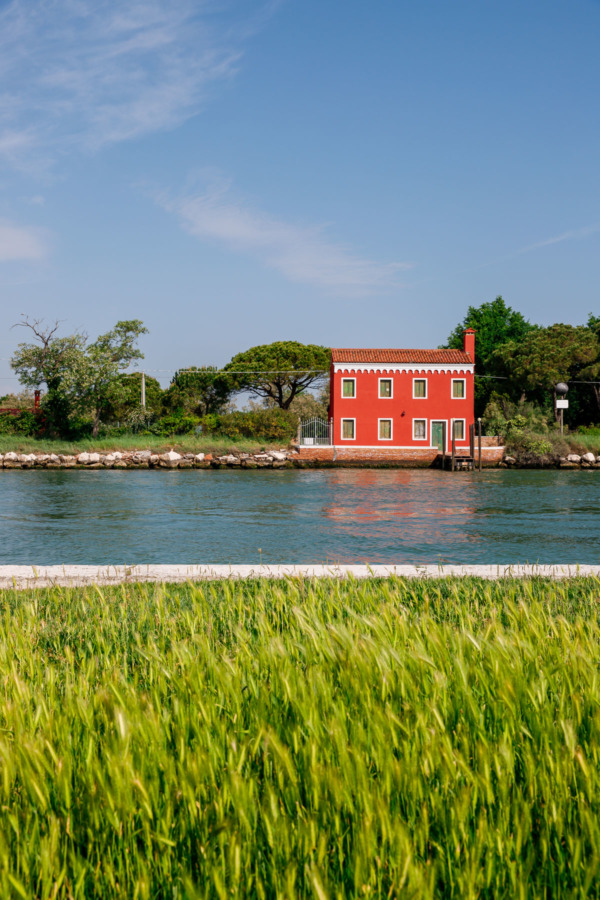 Bright red house on the water, Burano, Italy