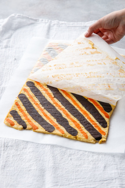 While the cake is still warm, peel off the parchment paper revealing the gorgeous striped cake roll!