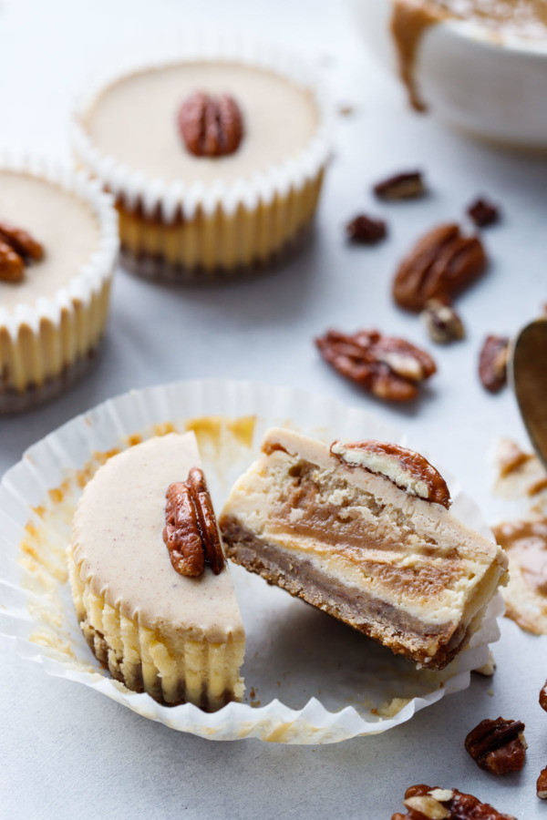 Pecan Praline Mini Cheesecakes, cut in half to reveal the swirl of pecan praline inside.