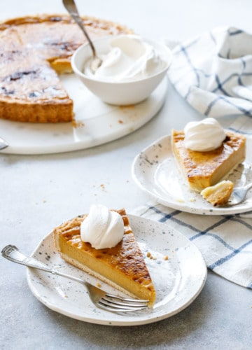Slice of Pumpkin Custard Tart recipe served with fresh whipped cream