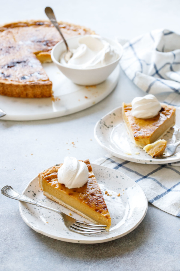 Slice of Pumpkin Custard Tart recipe served with fresh whipped cream