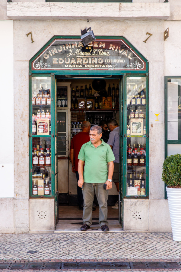Man standing in the storefront of Ginjinha Sem Rival in Lisbon, Portugal