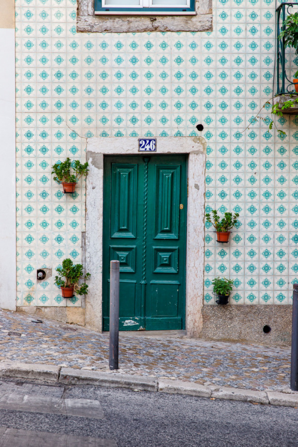Quaint green door and aqua tile facade in Lisbon, Portugal