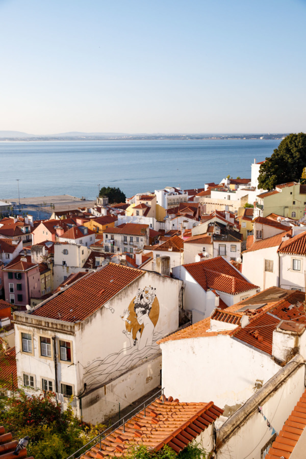 Looking out over the rooftops of the Alfama neighborhood in Lisbon, Portugal, with the Tagus river in the background.