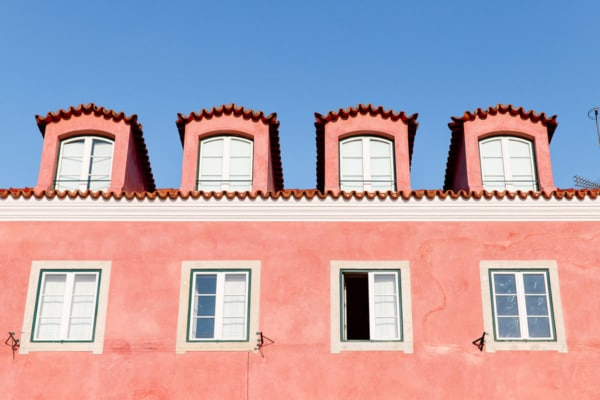 Coral pink building against a bright blue sky.