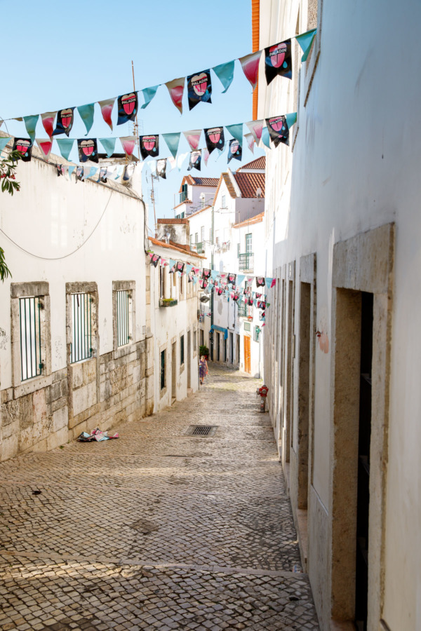 Narrow cobblestone street crisscrossed by colorful buntings in Lisbon, Portugal