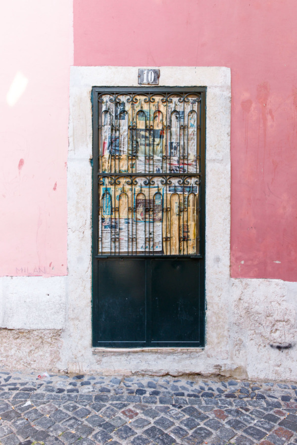 Colorful pink walls and ornate ironwork door in Lisbon, Portugal