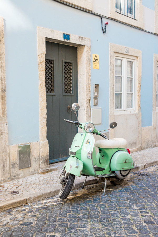Cute mint green scooter parked in front of a pastel blue building in Lisbon, Portugal