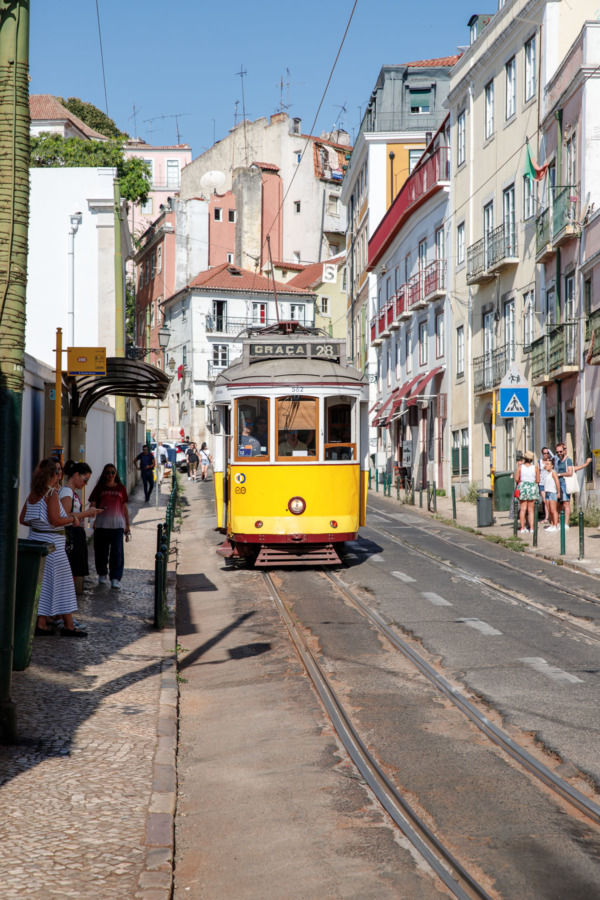 the 28E tram along a narrow street in Lisbon, Portugal