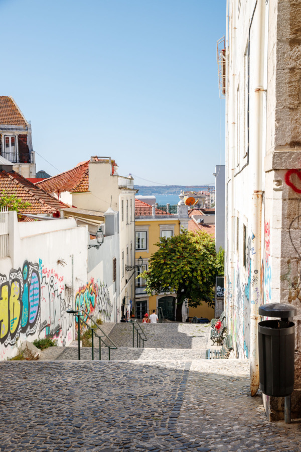 Down a colorful street with graffiti in Lisbon, Portugal