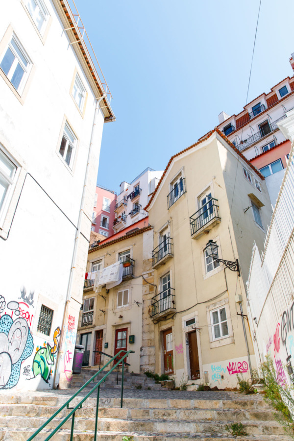 Looking up a steep street at pastel colored buildings in Lisbon, Portugal