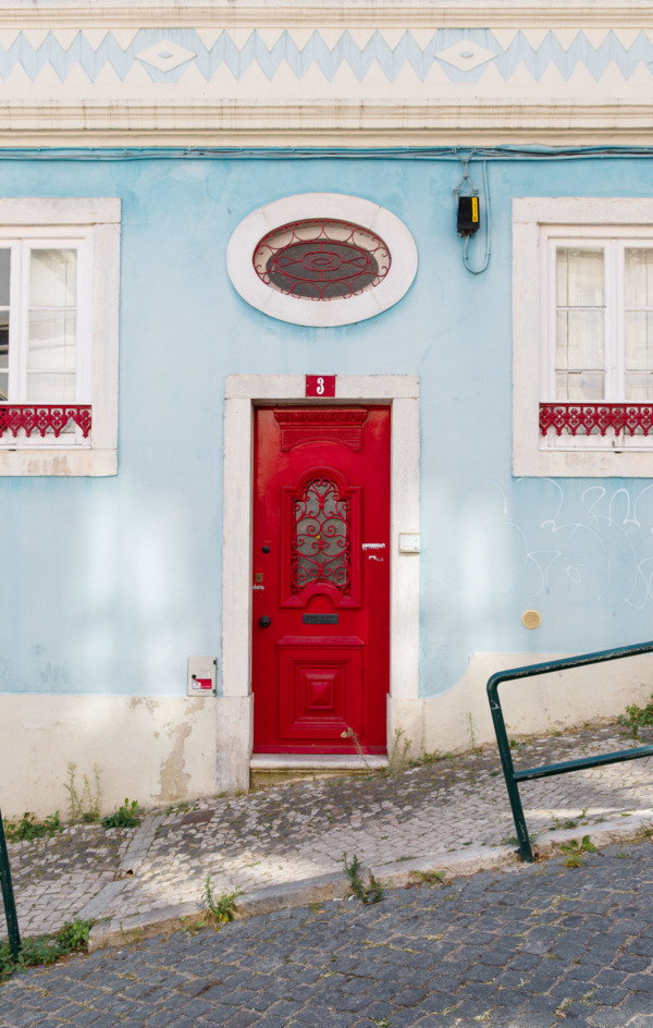 Cute red door on a pastel blue building in Lisbon, Portugal