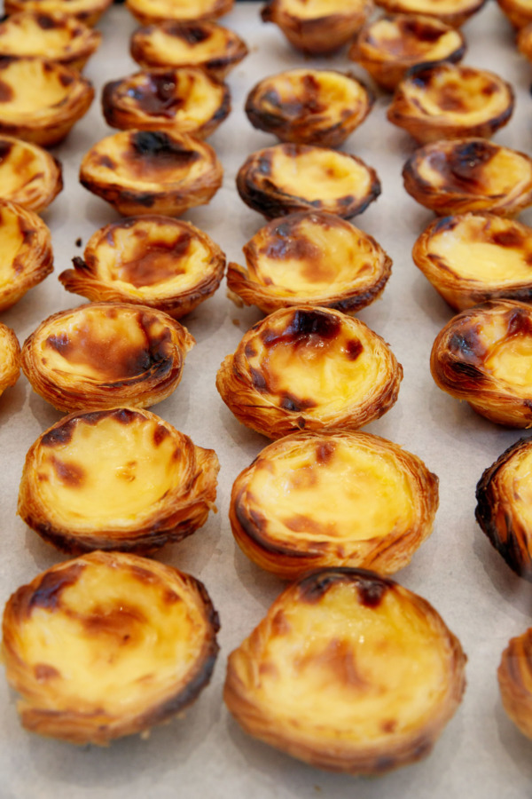 Dozens of freshly baked Pastéis de Nata tarts from Fábrica da Nata in Lisbon, Portugal