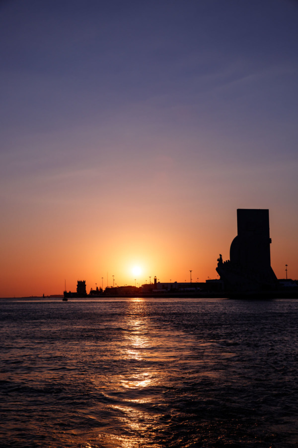 View from the river at sunset, looking back at the Padrão dos Descobrimentos and the Belém Tower in Lisbon, Portgual