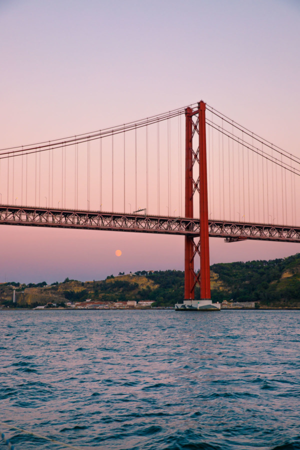 The moon visible at sunset underneath the 25 de Abril bridge in Lisbon, Portgual