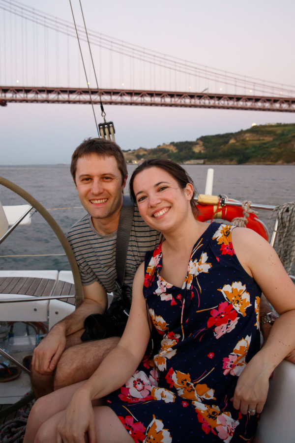 Lindsay & Taylor in a sailboat on the Tagus river in Lisbon, Portgual, with the Ponte 25 de Abril in the background