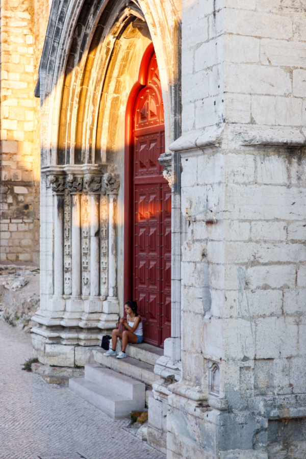Girl sitting in front of the large red side door of the Carmo Convent in Lisbon, Portgual