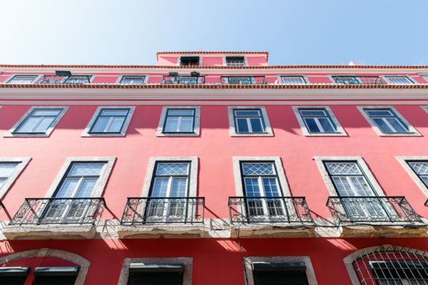 Looking up at a pretty coral pink building and blue sky in Lisbon, Portugal