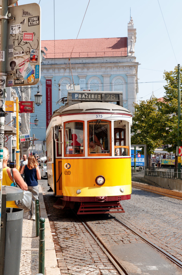 The 28E tram letting people on at a bus stop in Lisbon, Portugal