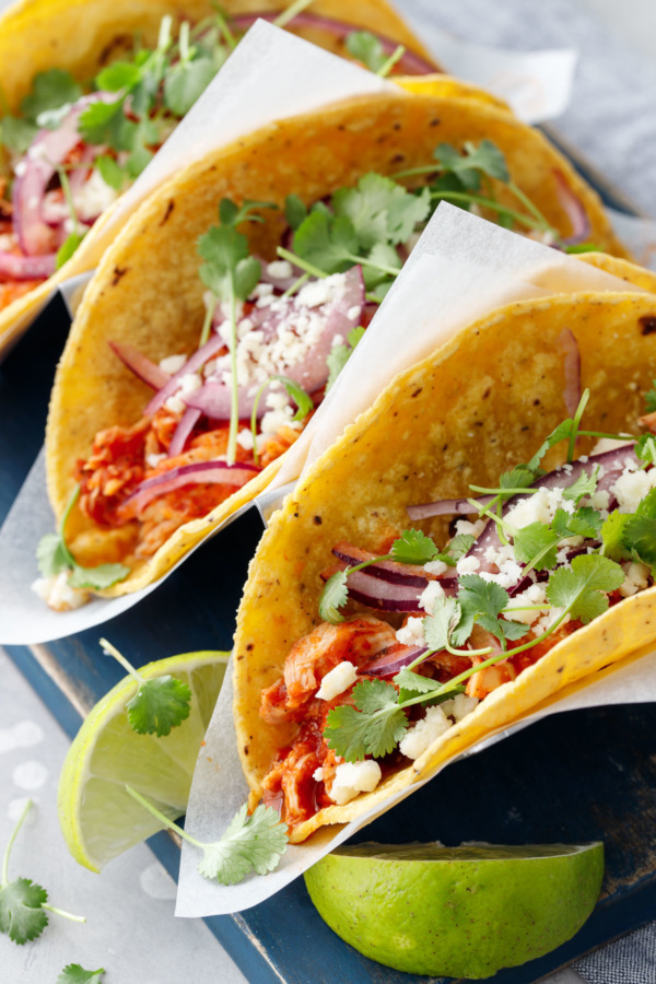 Close up of chicken tinga tacos in corn tortillas with a slice of lime.