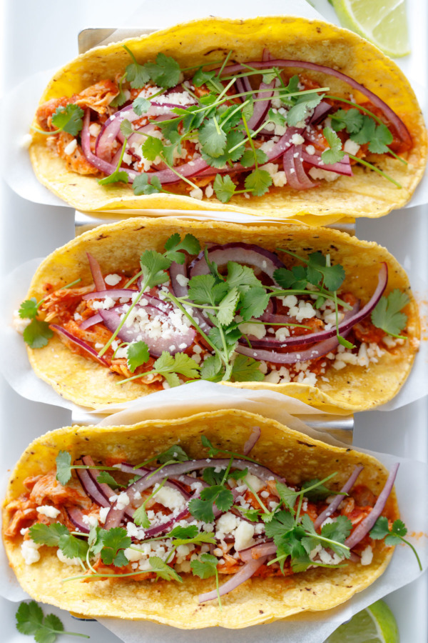 Overhead of three chicken tinga tacos topped with pickled red onion, crumbled cotija cheese, and fresh micro cilantro