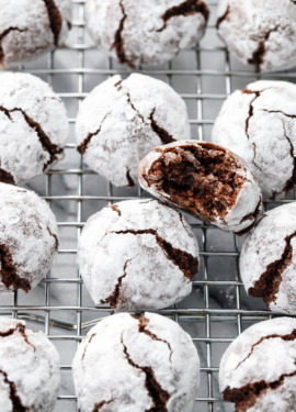 Rows of Chocolate Amaretti Cookies on a wire cooling rack, with one cookie with a bite taken out of it.