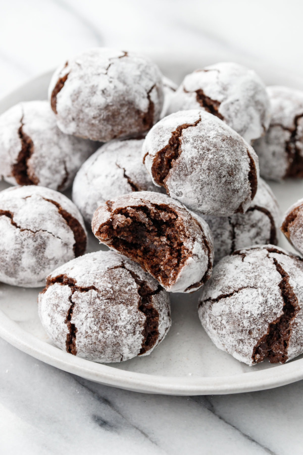 A plate full of Chocolate Amaretti Cookies, one cookie with a bite taken out of it.