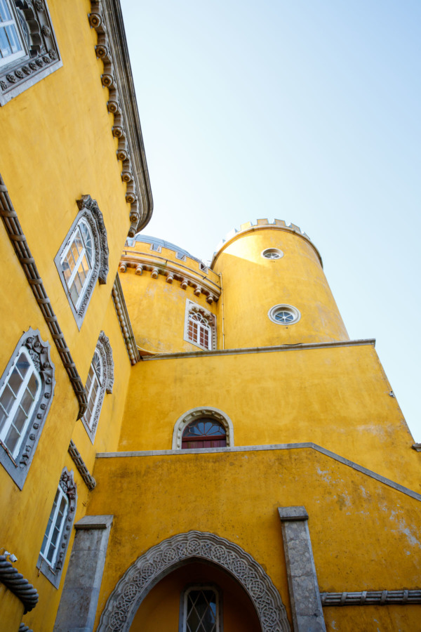 Looking up at the bright yellow walls and towers of the Pena Palace, Sintra, Portugal