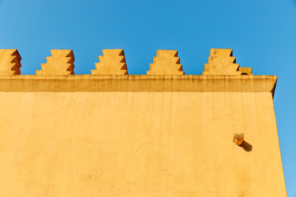 Geometric yellow walls against a bright blue sky in Sintra, Portugal