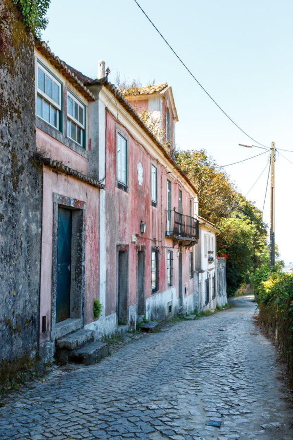 Cobblestone alley way lined with pink houses in Sintra, Portugal