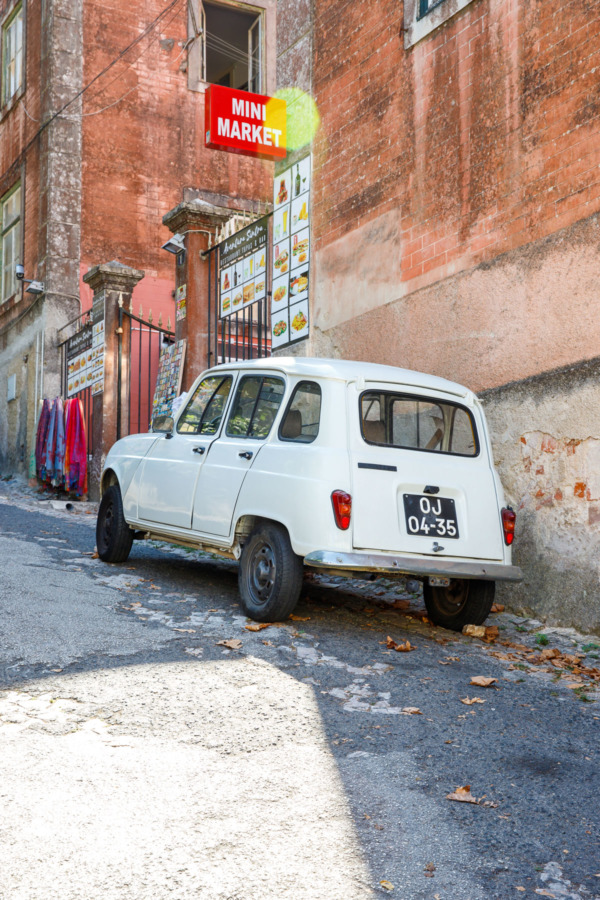 A cute little car parked on a steep incline in Sintra, Portugal