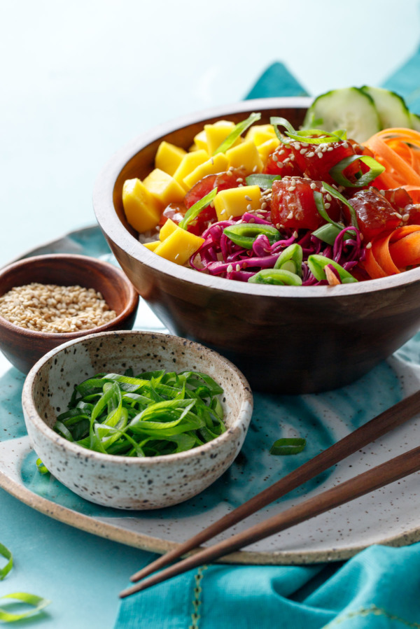 Bowl of Ahi Mango Poke, with smaller bowls of green onions and sesame seeds on the side for garnish.