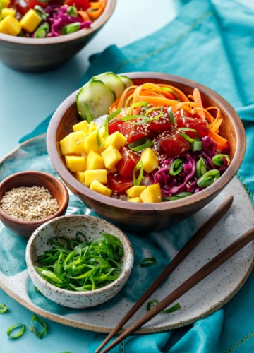 Ahi Mango Poke served in a wooden bowl on a turquoise background.