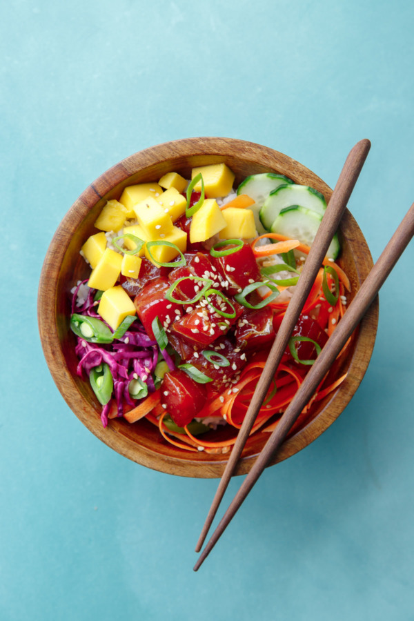 Overhead shot of a single wooden bowl with Ahi Mango Poke and chopsticks, on a turquoise background.