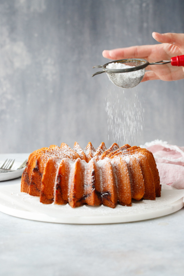 Dusting powdered sugar over a beautiful bundt cake