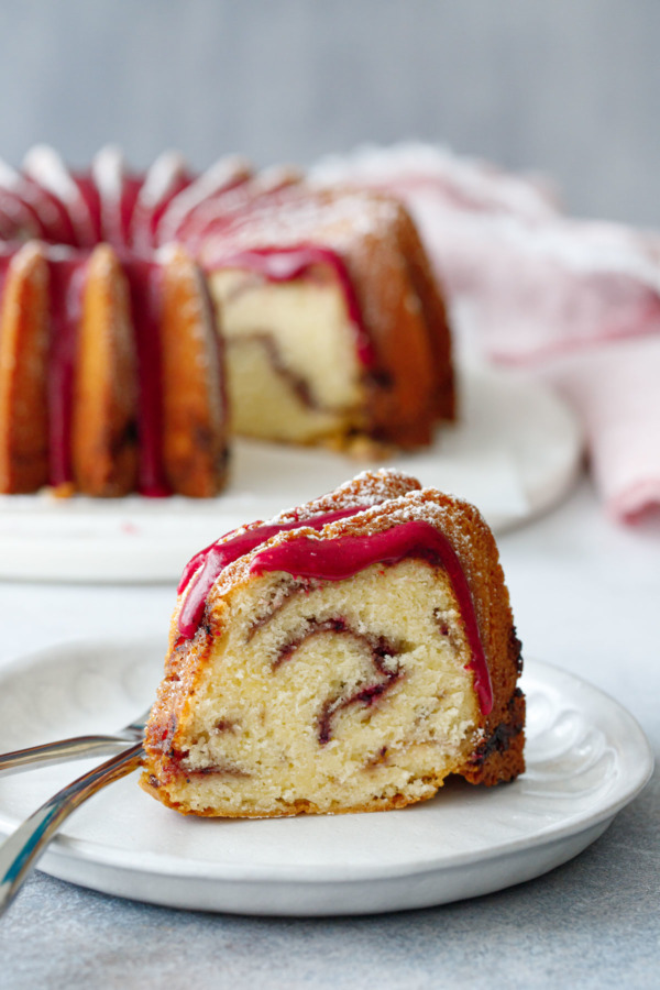 A slice of strawberry hibiscus swirl pound cake sitting on a plate, with the full bundt cake on a marble cake plate in the background.