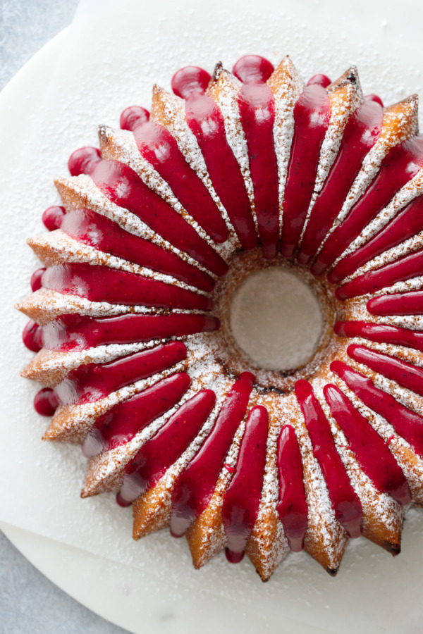 Top down view of a bundt cake, dusted with powdered sugar and drizzled with a bright pink strawberry hibiscus glaze.