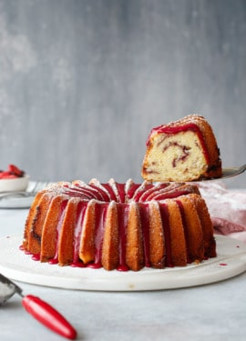 A slice of strawberry hibiscus pound cake being lifted with a cake server.