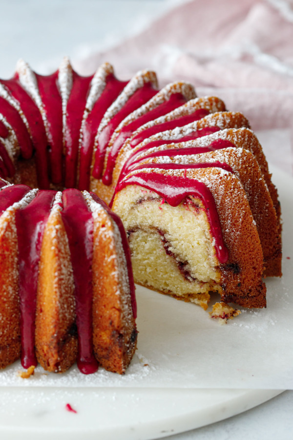 A brilliant bundt cake with a slice taken out of it, dusted in powdered sugar with a bright pink hibiscus glaze.
