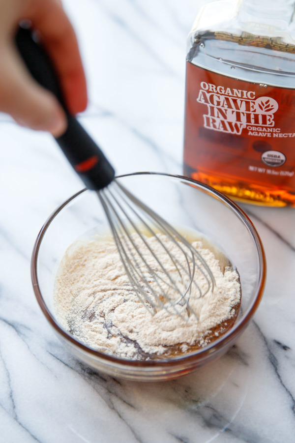 Whisking powdered pectin into a bowl with agave syrup.