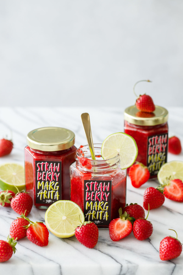 Three jars of homemade Strawberry Margarita Jam, one jar open with a gold spoon and a slice of lime on the edge, surrounded by fresh strawberries and limes.