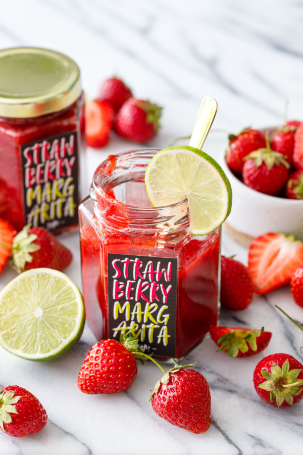Homemade strawberry margarita jam in hexagon glass jars with custom designed labels, surrounded by fresh strawberries and limes.