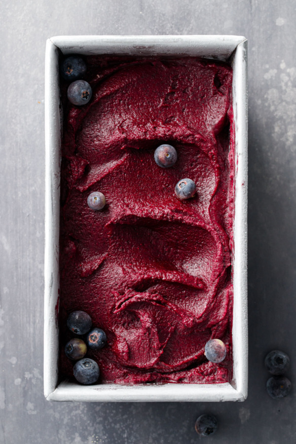 Overhead shot of metal loaf pan filled with a swirl of Blueberry Ginger Sorbet