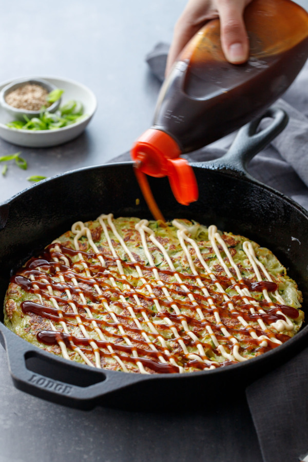 Drizzling okonomiyaki with kewpie mayonnaise and okonomi sauce