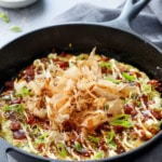 Cabbage & Zucchini Okonomiyaki, cooked in a cast iron skillet and topped with bonito flakes